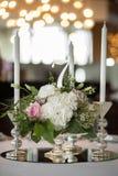 O ajuste da tabela do casamento é decorado com flores frescas e velas brancas Casamento floristry Ramalhete com rosas, hortênsia  foto de stock royalty free