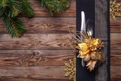 O ajuste de lugar da tabela do Natal decorou o guardanapo preto com forquilha e faca, flor do ouro e flocos de neve e pinho do Na Imagens de Stock