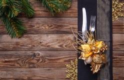 O ajuste de lugar da tabela do Natal decorou o guardanapo preto com forquilha e faca, flor do ouro e flocos de neve e pinho do Na Imagem de Stock