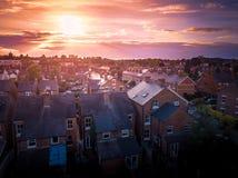 O ajuste de Sun com efeito atmosf?rico sobre casas brit?nicas tradicionais e ?rvore alinhou ruas fotos de stock royalty free