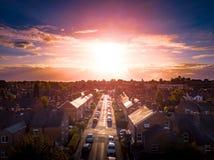 O ajuste de Sun com efeito atmosf?rico sobre casas brit?nicas tradicionais e ?rvore alinhou ruas fotografia de stock royalty free