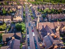 O ajuste de Sun com efeito atmosf?rico sobre casas brit?nicas tradicionais e ?rvore alinhou ruas imagens de stock royalty free