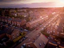 O ajuste de Sun com efeito atmosf?rico sobre casas brit?nicas tradicionais e ?rvore alinhou ruas foto de stock