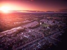 O ajuste de Sun com efeito atmosf?rico sobre casas brit?nicas tradicionais e ?rvore alinhou ruas foto de stock royalty free