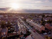 O ajuste de Sun com efeito atmosf?rico sobre casas brit?nicas tradicionais e ?rvore alinhou ruas fotografia de stock