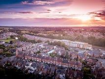 O ajuste de Sun com efeito atmosf?rico sobre casas brit?nicas tradicionais e ?rvore alinhou ruas imagem de stock royalty free