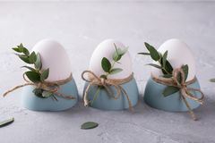 O ajuste festivo da tabela da Páscoa com galinha branca eggs em uns copos de ovos, ramos da folha do eucalipto Imagens de Stock