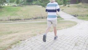 O albino do menino louro está correndo através do parque video estoque