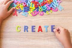 O alfabeto e a palavra de madeira coloridos CRIAM, entregam - o tipo em E alto Fotografia de Stock
