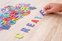 O alfabeto e a palavra de madeira coloridos CRIAM, entregam - o tipo em E alto Foto de Stock