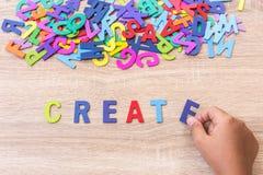 O alfabeto e a palavra de madeira coloridos CRIAM, entregam - o tipo em E alto Fotos de Stock Royalty Free