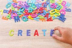 O alfabeto e a palavra de madeira coloridos CRIAM, entregam - o tipo em E alto Fotos de Stock