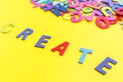 O alfabeto e a palavra de madeira coloridos CRIAM Vista superior em t amarelo Fotos de Stock