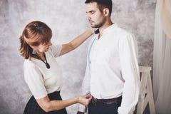 O alfaiate da mulher toma medidas com modelos masculinos Desenhador de moda s imagem de stock royalty free