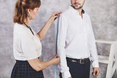 O alfaiate da mulher toma medidas com modelos masculinos Desenhador de moda s foto de stock royalty free