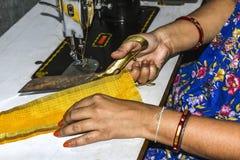 O alfaiate das senhoras da Índia que corta a roupa com scissor e que faz o vestido pela máquina de costura imagens de stock royalty free