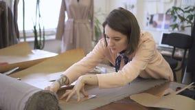 O alfaiate fêmea novo está fazendo marcações no tecido com o giz, estando na tabela no estúdio da costura, desenhador de moda est video estoque