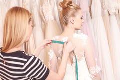 O alfaiate fêmea talentoso está fazendo a roupa nupcial Imagem de Stock Royalty Free