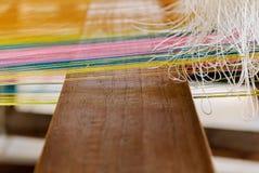 O algodão colorido de tecelagem rosqueia pelo tear de madeira do tradtional Imagens de Stock