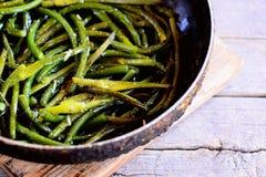 O alho verde fritado desengaça com especiarias em uma frigideira e em uma tabela de madeira do vintage Alimento simples e saudáve Fotos de Stock Royalty Free