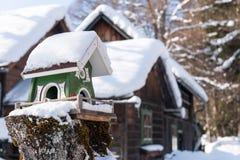 O alimentador caseiro do pássaro de madeira no inverno, sob a neve foto de stock