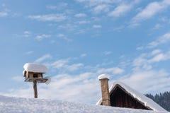 O alimentador caseiro do pássaro de madeira sob a neve no inverno fotografia de stock royalty free