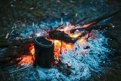 O alimento é cozinhado sobre um fogo em um potenciômetro de marcha retro do vintage velho Fotografia de Stock