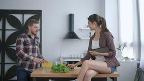 O alimento útil, indivíduo feliz prepara a refeição saudável do vegetariano no jantar e a menina que senta-se na mesa de cozinha  vídeos de arquivo