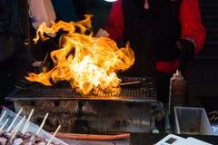 O alimento coreano da rua, espeto do calamar está cozinhando com chama fotos de stock