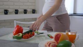 O alimento natural para a gravidez, a menina de maternidade com abdômen grande está cozinhando a salada útil para o almoço saboro video estoque