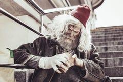 O Almsman que senta e que conta o dinheiro pequeno recebeu pelo dia imagem de stock