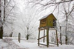 O alojamento coberto de neve de madeira e das crianças do ` s em uma árvore fotos de stock royalty free