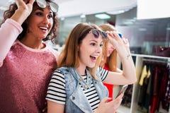 o Alto-ângulo disparou dos amigos fêmeas à moda novos que vestem óculos de sol na moda e roupa que têm o divertimento no shopping Fotos de Stock Royalty Free
