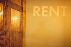 O aluguel, a inscrição na parede brilhante nas letras brancas foto de stock