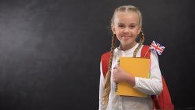 O aluno contente guarda livros com a bandeira de Grâ Bretanha, pronta para aprender a língua estrangeira filme