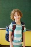 O aluno da escola primária está na classe perto de uma placa foto de stock