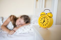 O aluno dorme na cama o despertador amarelo está no pulso de disparo do ` das mostras sete o da tabela fotos de stock