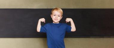 O aluno mostra os músculos na frente do quadro-negro na escola primária fotos de stock