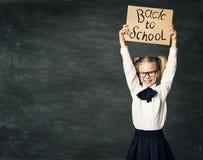 O aluno sobre o fundo do quadro-negro, menina anuncia a placa foto de stock
