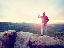 O amador toma fotos com o telefone no pico da rocha Paisagem sonhadora, cair de Sun no horizonte Imagens de Stock
