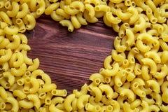 O amante da massa do macarrão, fundo seco da textura da massa do macarrão com coração dá forma ao espaço da cópia imagem de stock royalty free