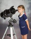 O amante da menina da astronomia com interesse olha no ocular do telescópio fotografia de stock royalty free