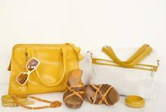 O amarelo bonito do verão ensaca com sandálias e os acessórios de harmonização Imagem de Stock