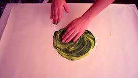 O amarelo de mistura da pintura com verde e as mãos que mancham-se no branco surgem filme