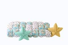 O amarelo e a estrela cinco-aguçado feita malha azul esverdeado deram forma a descansos e a cobertor dos retalhos no fundo branco Fotografia de Stock Royalty Free