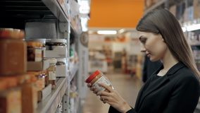 O amendoim de compra de sorriso do consumidor de mulher cola o frasco com mel branco no café Imagem de Stock