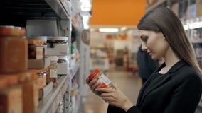 O amendoim de compra de sorriso do consumidor de mulher cola o frasco com mel branco no café Foto de Stock Royalty Free