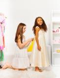 O amigo ajuda uma outra menina a caber o vestido bonito Fotografia de Stock