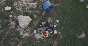 O amigo da vista aérea tem uma fogueira no meio da montanha, e barraca atrás deles, têm a despesa uma boa estadia vídeos de arquivo