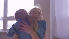 O amor à irmã, menina apressa-se em uns braços mais velhos da irmã em casa e dá-se seu abraço grande video estoque